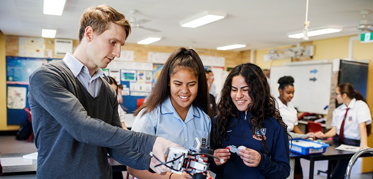 Two girls and a male teacher build a lego robot.